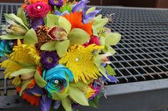 Bridal Bouquet of yellow spider mums, rainbow roses, green cymbidium orchids, orange gerberas, pink roses, purple asters. www.genesbeaverfloral.com