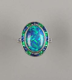 A black opal, sapphire and emerald cluster ring,  the oval black opal cabochon within a border of scissor-cut sapphires and emeralds, to sapphire shoulders, the mount with engraved foliate detail