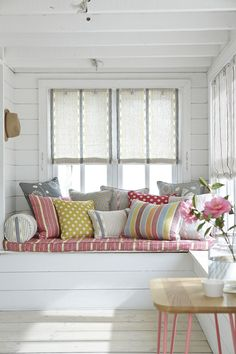 Get the most out of a sunny window by having a lift-up seat built underneath it, perfect for hidden storage. Add a covered seat pad and a colourful mix of cushions like these from Vanessa Arbuthnott. Find more ideas at housebeautiful.co.uk