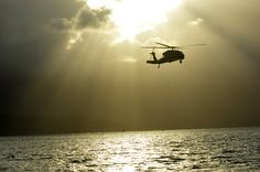 A UH-60 Blackhawk with US Army 25th CAB prepares to execute helocast with Navy SEALs from SWG3 at MCAS Kaneohe Bay, Hawaii.  (Photo by Captain Richard Baker, 18 JUN 2013.)