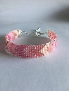 Fun bead loom bracelet in a chevron pattern with various shades of pink and sliver accent that can stacked with others or worn alone. Made with delica beads and finished with silver ribbon clasp and two inch extension chain. If you need something longer or shorter or would like this