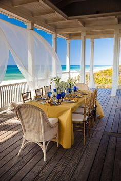 Porch dining table setting with yellow white and royal blue next to the ocean, beach.  White sheer curtains blowing in the wind.