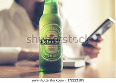 Milan, Italy - January 16, 2014: Woman Drinking Heineken Beer Glass Bottle 33 Cl. Heineken International Is A Dutch Brewing Company, Founded In 1864 In Amsterdam, Famous All Over The World. Foto Stock: 172221185 : Shutterstock BUY IT FROM $1