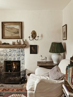 The sitting room at Docker Nook, with a fireplace surrounded by Delft tiles and a cozy club chair. Dining Room Walls, Living Room, Cottage Living, Living Spaces, Pale Blue Walls, Headboard Cover, Houses In France, Delft Tiles, London Apartment