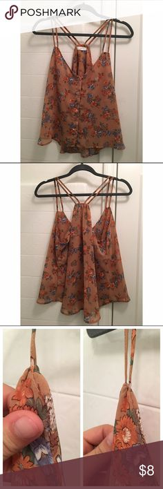 Floral Crisscross Tank Orange and floral patterned tank top, with crisscross straps and a button up front. Super cute, has gotten some love but in good condition. No pulls or fraying, only small tear is by the straps on the right side in the seam, which is barely noticeable when wearing. Shown side by side (left pic) is the tear, (right pic) is when hanging/worn. Adorable for spring under a cardigan or with jeans! Mine Tops Tank Tops