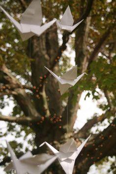 Origami birds are suspended from the trees at this outdoor party, adding a delicate, sculptural touch!