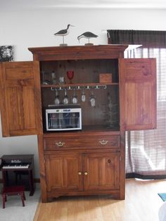 This is an armoire we canged into a wine bar. Had to cur a hole in the back for the small wine fridge. Bar Hutch, Armoire Bar, Mini Wine Fridge, Wine Bottle Corks, Wine Glass Holder, Cool Bars, Kitchen Gadgets, Home Remodeling, Man Cave