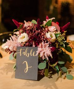 i know you wanted low centerpieces - something like this could be super pretty! also really like the table number too!