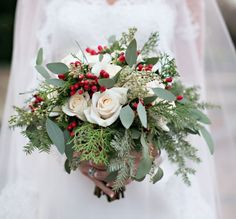 A loose bouquet of cedar foliage, seeded eucalyptus, red hypericum berries, grey dusty miller, ivory roses, ivory spray roses, and pinecones wrapped in black velvet ribbon tied in a bow