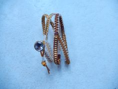 bracelet tissé avec perles de verre et bouton (fait plusieurs fois le tour du bras)