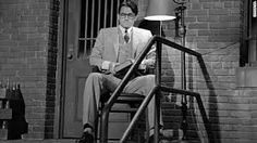 Atticus sitting in front of jail cell where Tom is staying.