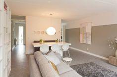 Tafel tegen de wand tussen keuken en hal. Afwisseling van wit en houten meubels, rustige basiskleuren en een witte rand aan de bovenzijde van de muur. Metamorfose van rtl-woonmagazine afl.2-2012