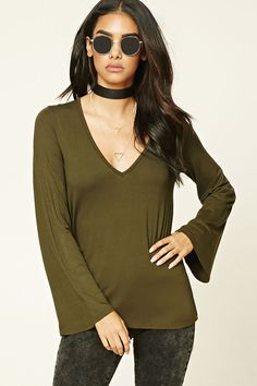 A knit top featuring a V-neckline, long bell sleeves, and a flowy silhouette.