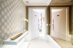 Hall de entrada de apartamento com papel de parede da Bucalo Book Waverly, painel em espelho bronze da Pura Art Vidraçaria e prateleira de marcenaria iluminada da Espaço Interferência. Projeto realizado pela Le Haus Arquitetura em parceria com a Elementhos Projetos.