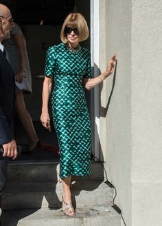 Anna Wintour wears a slim green patterned dress with a beaded necklace.