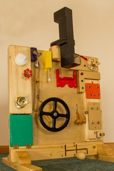 "Has a periscope, steering wheel and shifter, throttle, lock box with coin slot, knobs and buttons, lights and buzzers and a ""peek a boo"" slide Found other toys but he would have out grown them in a few months so I built this for years of fun and learning. I'm already planning the 5 year old version. #Busyboard, #Kids"