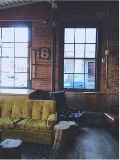Living room is industrial and comfy at the same time. Bricks, large black windows, earthy toned.