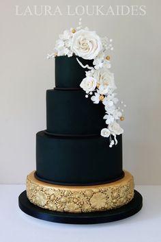 Una creación de Laura Loukaides con bordes rectos y perfectos en negro dorado y un detalle de flores blancas.