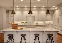 White kitchen with large island and industrial counter stools, love the pendants.