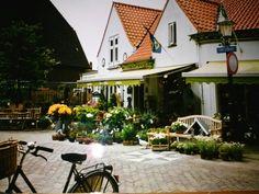 Voormalige bloemenwinkel, nu een brasserie met terras met een klein pleintje ervoor.