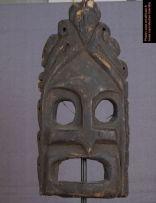 Masque très archaïque en provenance des îles Moluques. Il est de forme triangulaire, bordé de vaguelettes. Une tête doiseau figure au sommet du triangle. Le visage est est partagé en 4 par le nez et les ailes du nez. Les yeux et la bouches sont béants. On dirait que ce masque va parler. Il fait penser à une gorgone.