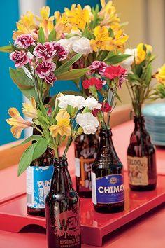 Não só garrafas de vinho viram vasos para flores. As de cerveja também podem desempenhar bem este papel. Elas podem voltar à mesa com os rótulos coloridos e diferentes. Produção de Henrique Morais