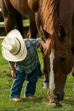 little cowboy checking out his horse