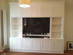 High and low level shaker cabinets. Central TV and bookcases either side. …