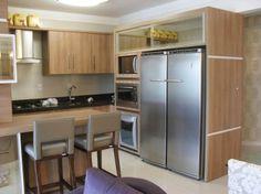 Cozinha completa e planejada em tons de madeira são opções certeiras para deixar sua casa ainda mais moderna.