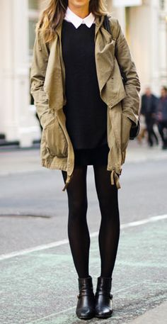 collared white shirt under black sweater, black mini skirt with tights, black shoes and khaki jacket