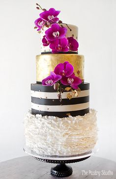 gold metallic black stripes and ruffles with bright orchids wedding cake showpiece