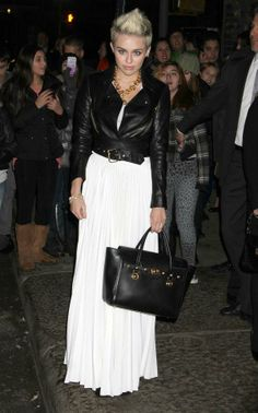 46ac70fbcbd4 Miley Cyrus Wears A Black Cropped Leather Jacket Over White Maxi Dress.  Versace