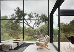 Rural house outside Melbourne by Studio Four with a blackened timber exterior and terraces that step down a hill.