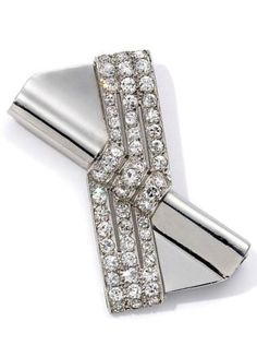 An Art Deco platinum and diamond brooch by Cartier Paris, platinum, folded over a diagonal cylinder and crossed with circular brilliant and single cut diamonds, with galleried edge, 4cm across, Cartier, Paris, circa 1925,. Cartier Poincon for 1922-1929, engraved 'Cartier', with French platinum guarantee stamp.