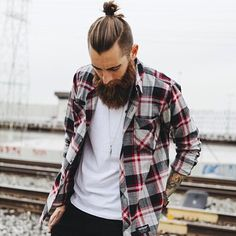 Trevor Jon Wayne (@trevorwayne), pulling out the killer top knot - epic beard combo.  by @gilsphotography  #beards #beardlife #topknot