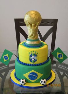 World Cup Cake - This is a cake i made for a man who loves soccer and the World Cup. He is a the biggest fan of Brazil ever! I made the World cup from RKT and fondant. Everything on this cake was hand cut using fondant and a little tylose, including the flags and emblems. Soccer balls are also fondant as well, thanks for taking a peek, enjoy!