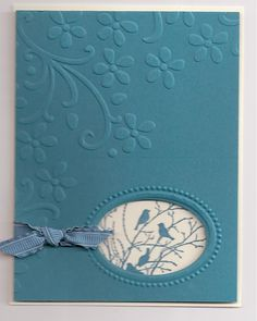 handmade card ... blue ... embossing fold flower flourish ..... knotted ribbon ... die cut oval window ... blue birds on branches inside ... Stampin' Up!