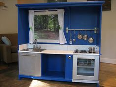 My little one is becoming more and more interested in the kitchen when I'm in there, so I started looking around for play kitchens.  I found this one and it's *so* cool that it was made from an old entertainment center!