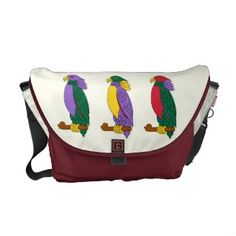 Colorful Cute Parrots Medium Courier Bags. This Rickshaw Messenger Zero bag features three bright colorful cartoon parrots with purple, yellow, red and green plumage, and beaks and claws in yellow standing on a brown branch on the flap against a background of ivory. There are more parrots on the back of the bag and on the inside.