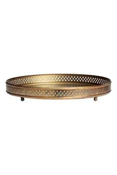 Round metal tray: Round metal tray with a perforated pattern around the rim and small round feet. Height 4.5 cm, diameter 30 cm.