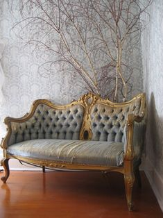 Frenchy Sofa. love the color of the wall and the dried 'tree', or cluster of branches, in the background