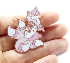 A hard enamel metal pin featuring a four tailed japanese kitsune with a sakura blossom pattern. This pin is made from a high polish shiny copper with layers of hard enamel colour. This pin is strong, durable and waterproof. This pin measures 4cm by 4cm (approx 1.5in x 1.5in) and has a