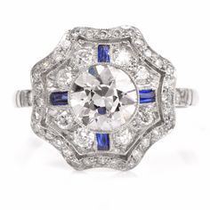 This vintage diamond engagement ring is finely handcrafted in solid platinum. It is centered with one bezel-set round European-cut diamond of approx. 1.00cttw, I color, VS2 clarity. This artfully designed floral motif plaque is adorned with 4 French cut baguette sapphires of approx. 0.15cts and some 48 round-cut diamonds of approx. 0.72cts, I color and VS1-VS2 clarity, within finely mille grained frames. This alluring Art Deco engagement ring remains in excellent condition. Weight: 3.7…