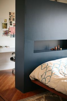 Headboard as room divider between bedroom and office space (rear of headboard functions as a bookcase)