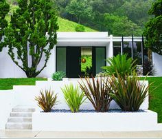 retaining walls and planters made of concrete -filled with plants and grey stones. use instead of brick walls