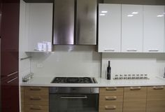 White quartz worktop with stainless steel appliances and glossy finishes. Modern kitchen designed by decades+