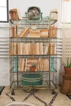 Our Brass Shelves decked out with neutral stacks of books + sea green props for the Cancer Zodiac Style. #PatinaZodiacStyle | Patina