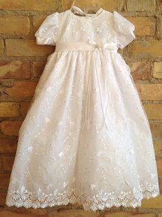 Gorgeous organza baptismal in white with stitched floral detail. Dress comes with matching bonnet and buttons/ties in back