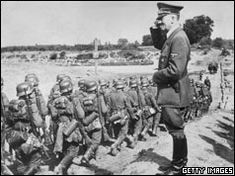 Adolf Hitler salutes his troops as they march towards Poland