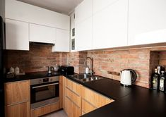plan de travail cuisine en granit noir, armoires en blanc et bois et mur en brique